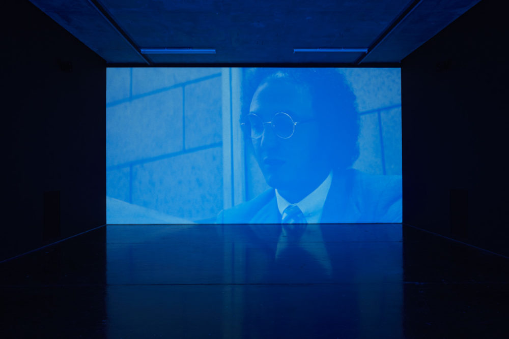 Installation view of Savage, I Asked You a Thousand Times (2011). A blue hued projection of a man in a suit.