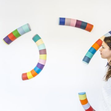 Colourful, curved tubes are suspended in air. A woman studies them.