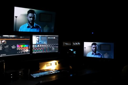 An edit suite shows several screens, digital tools and a keyboard.