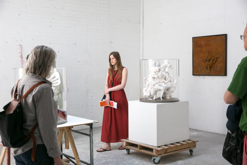 Three visitors look at sculptural work in an artists' studio.