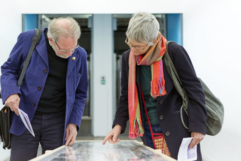 Two visitors study a table top at Open Studios 2017.