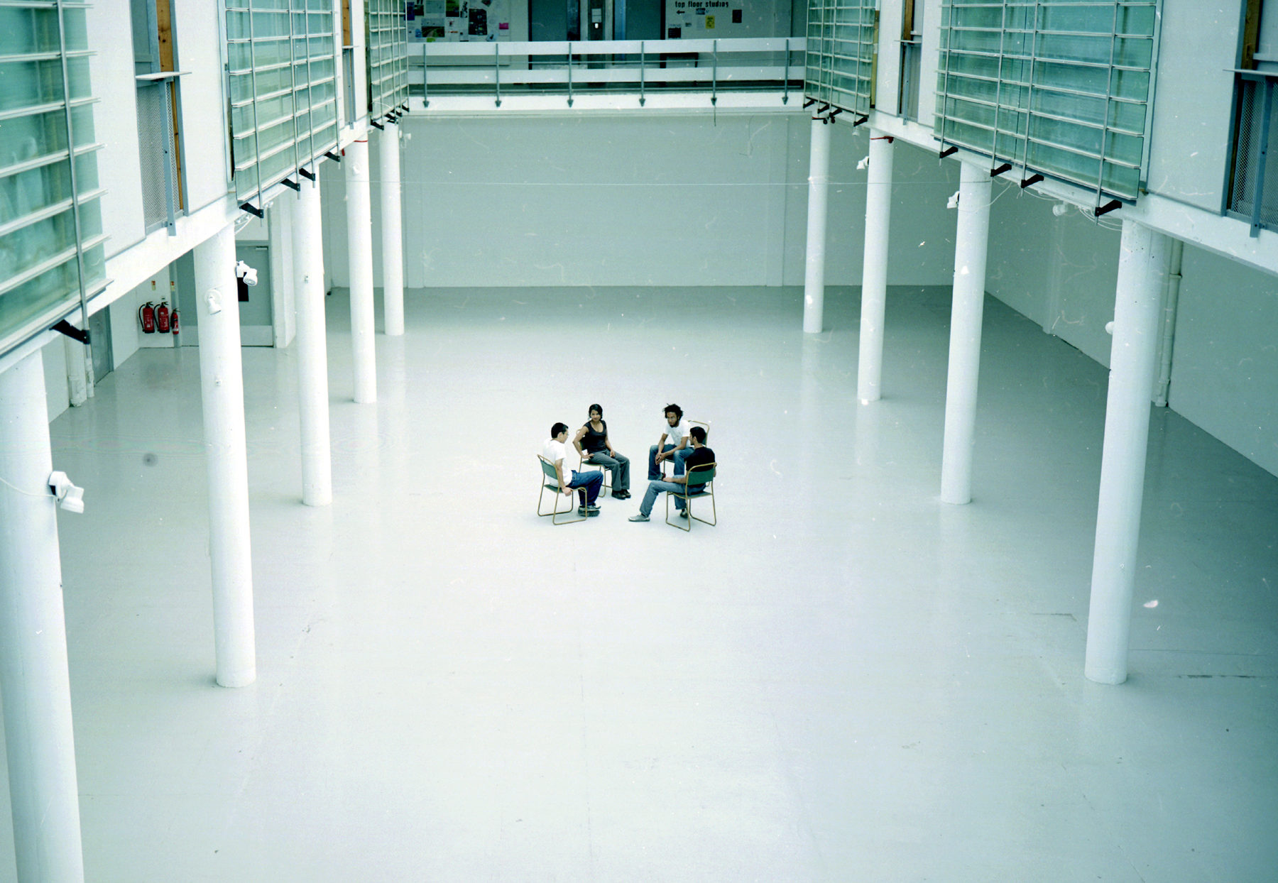 Installation view of Spin Cycle (2004). Four people sit on chairs facing one another in the centre of a white, bright gallery.