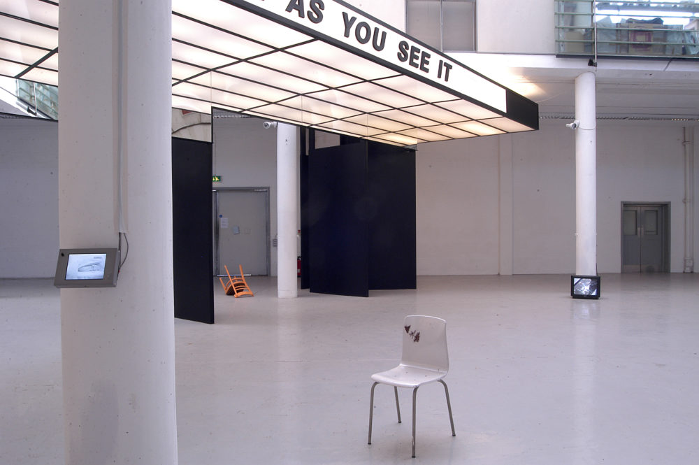 Installation view of Spin Cycle (2004). A canopy that looks like a cinema entrance hangs from the gallery ceiling,
