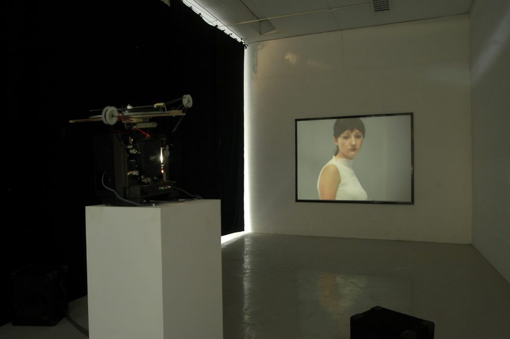 Installation view of Spin Cycle (2004). A projector screens a close up of a downcast looking woman on a wall.