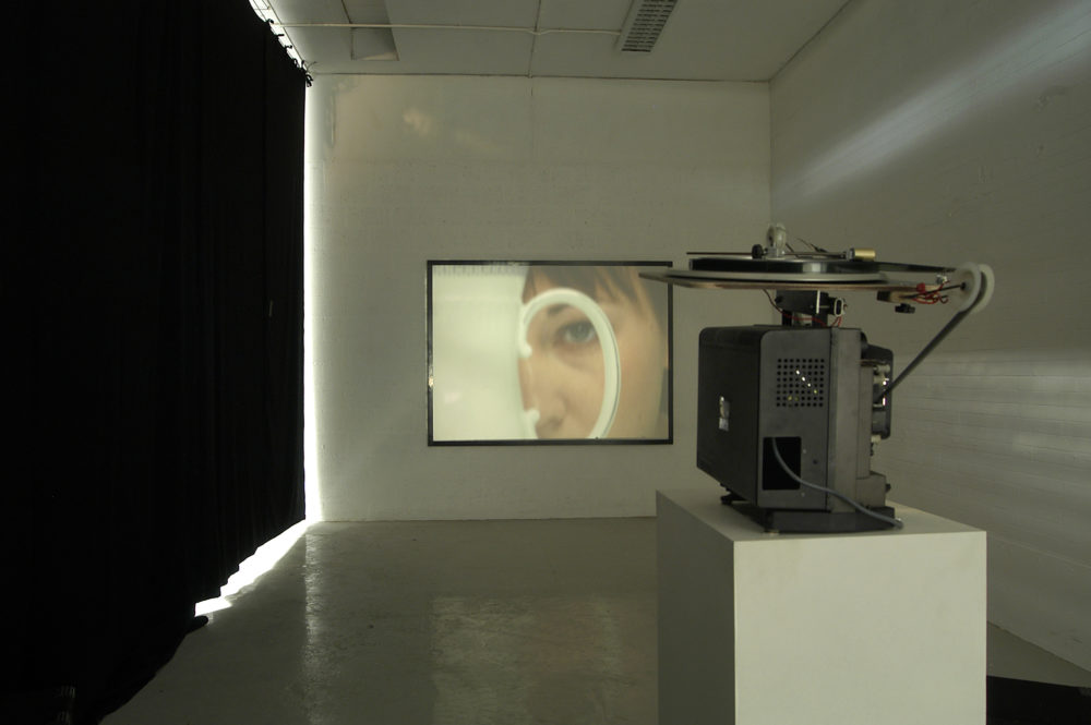 Installation view of Spin Cycle (2004). A projector screens a close up of a woman viewed through the handle of a jug on a wall.