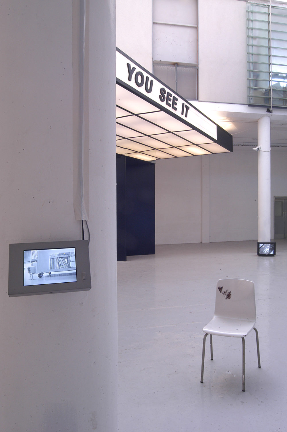 Installation view of Spin Cycle (2004). A small screen is attached to a pillar. Behind it is a plastic moulded chair.