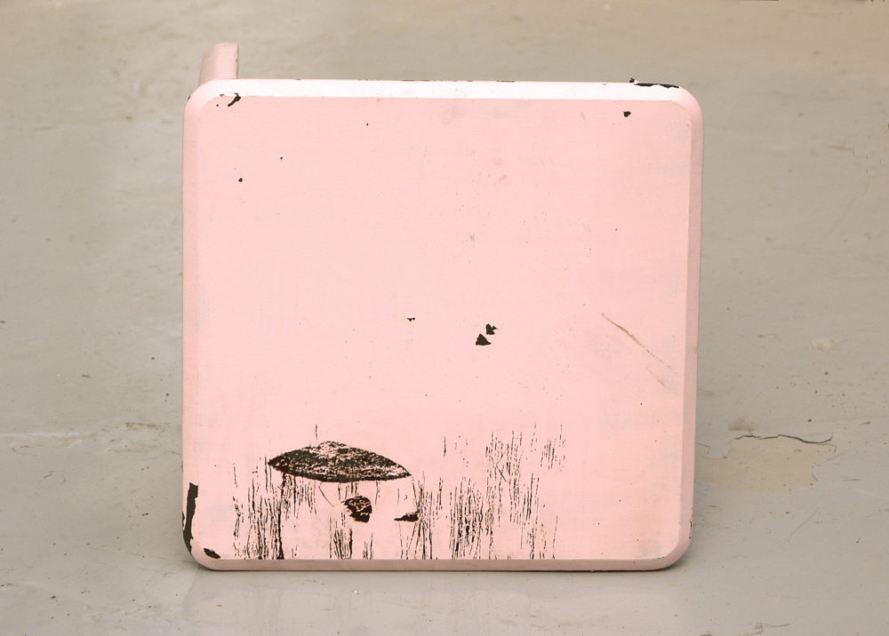 Installation view of Spin Cycle (2004). A wooden square stool that is painted baby pink lies on its side.