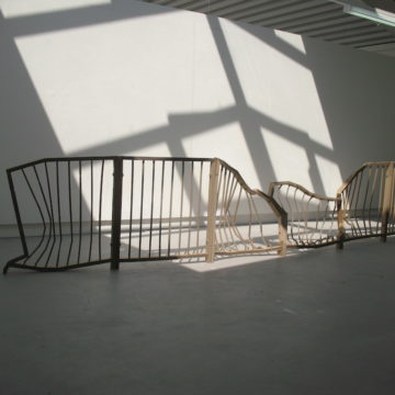 Sculpture: A damaged metal fence stands in a gallery. It is bent out of shape, especially in the middle.