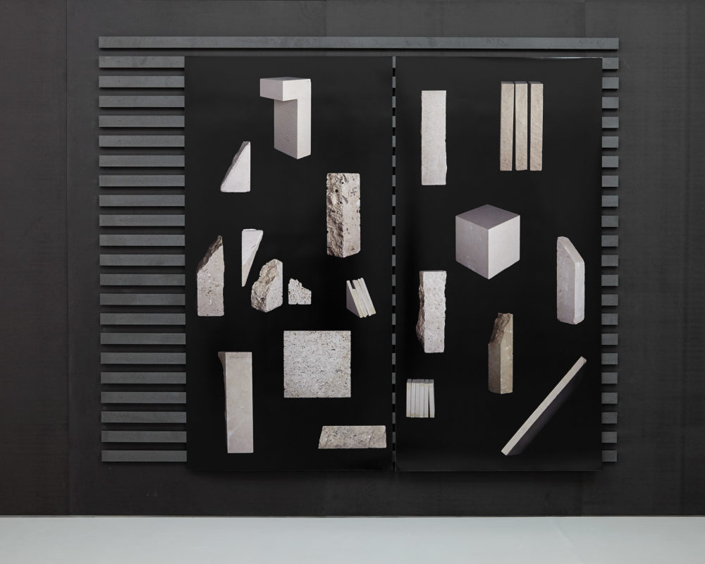 Computer generated illustrations of rocks are printed on black paper and applied to wooden slats.