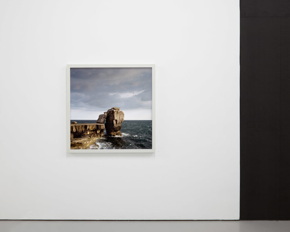 Install shot: A photo of crashing waves and a rocky outcrop is framed and hung on a white wall.