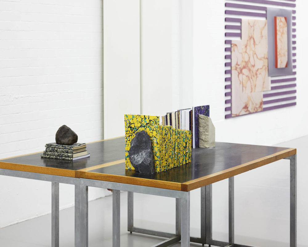 Installation shot: A table in the gallery has marbled paper covered books arranged atop it, using rocks as book ends.