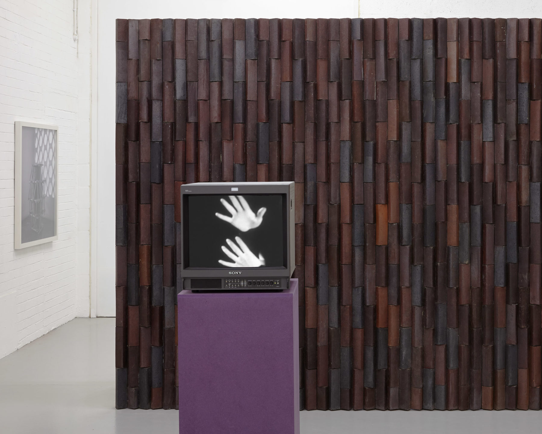 A screen in the gallery shows two white hands set against a dark background. This stands in front of a brick wall.