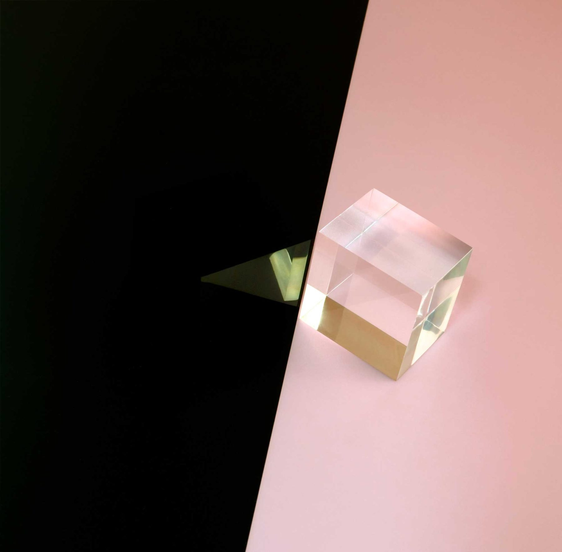 Installation view of Suzanne Mooney, The Edge of Collapse (2011). A clear perspex cube sits on the edge of a split between baby pink and black.