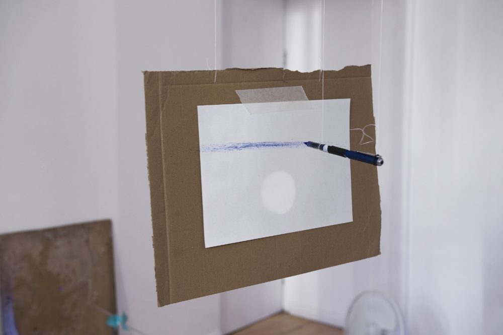 A blue pen is suspended from the ceiling horizontally. A white piece of paper is also suspended, but vertically. The blue pen is drawing an uneven line on the paper.