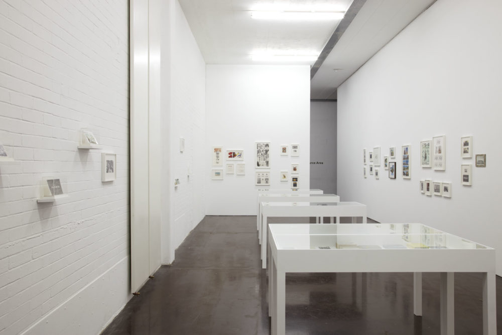 Installation view of The Artists' Postcard Show (2012). Five white table plinths with perspex tops hold postcards, as do frames on the wall.