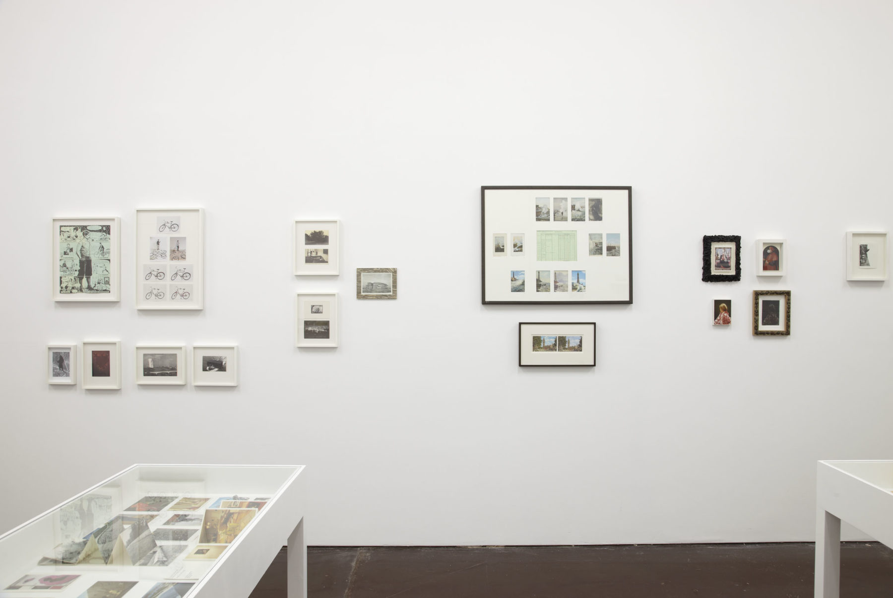 Installation view of The Artists' Postcard Show (2012). Various postcards are displayed in museum cases and hung on the wall in frames.