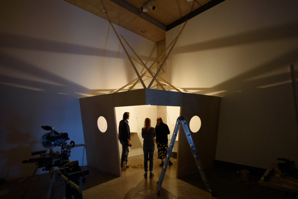 Installation shot: Three technicians work to erect a wooden structure in a white walled gallery.