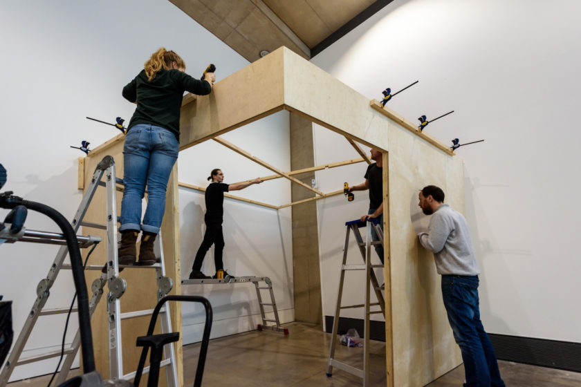 Installation shot: Four technicians work to erect a wooden structure in a white walled gallery.