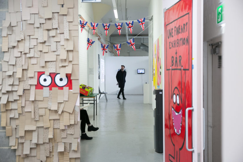 A visitor studies the art on display at UWE's graduate show 2017. Some bunting decorated with the Union Flag hangs with 'Bloody Hell' written across it.