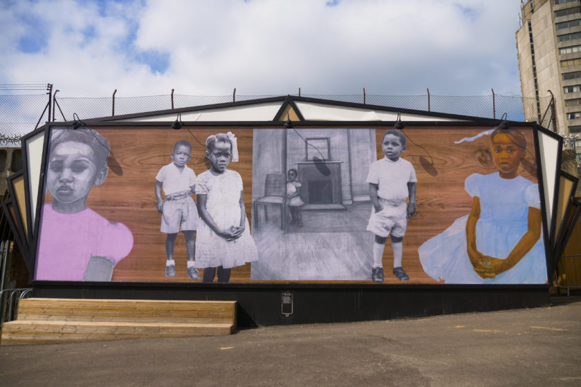 Site specific mural. Six young children of colour are imposed on a large wooden building side. Three of the children have been drawn, three are photographs.