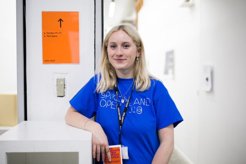 A volunteer wears a blue t-shirt and smiles directly at the camera at Spike Island Open Studios 2018.
