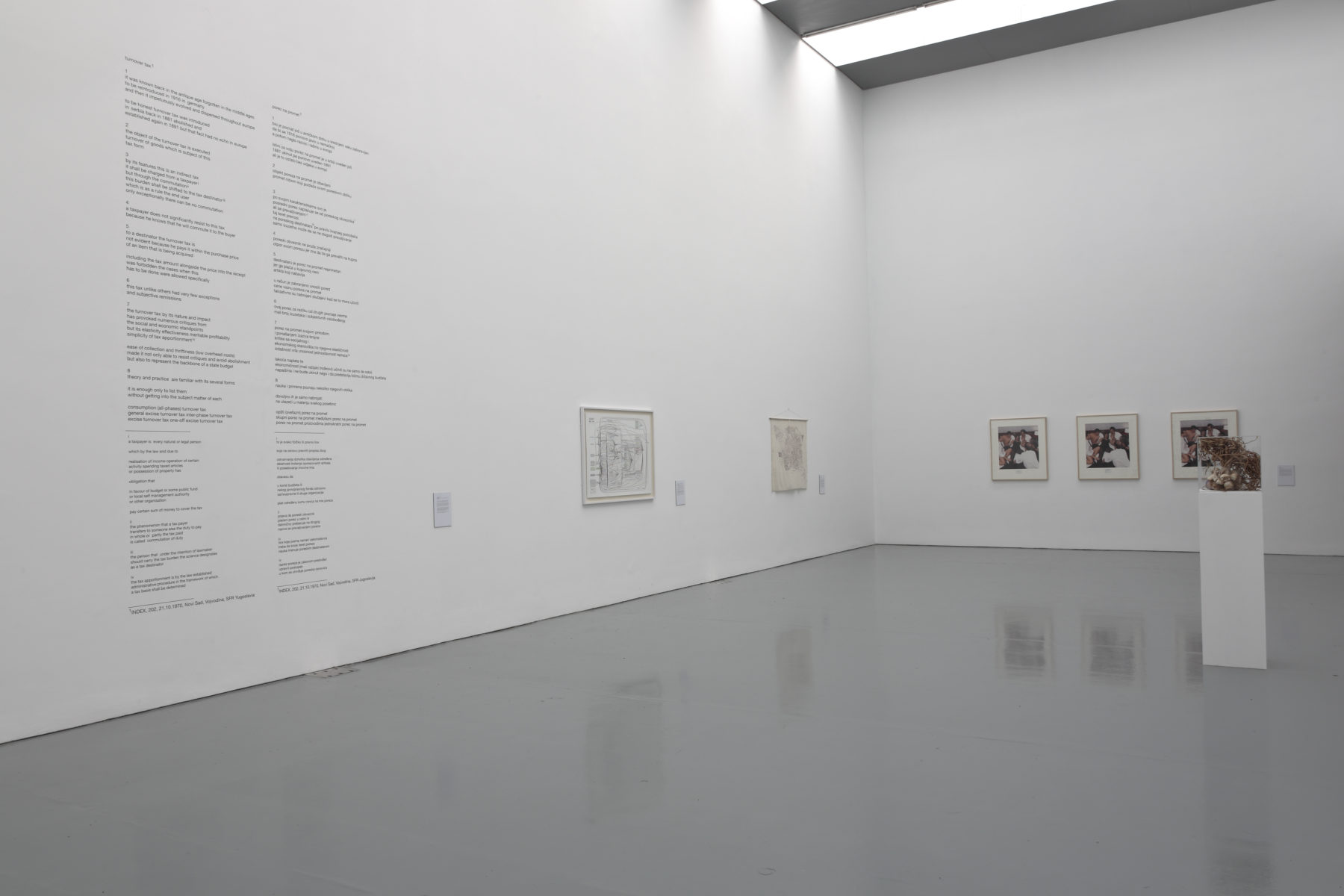 Installation view of Wealth of Nations (2010). The gallery is light and the walls are white. Five pictures hang on the walls and a plinth has a sculpture made from twigs atop it.