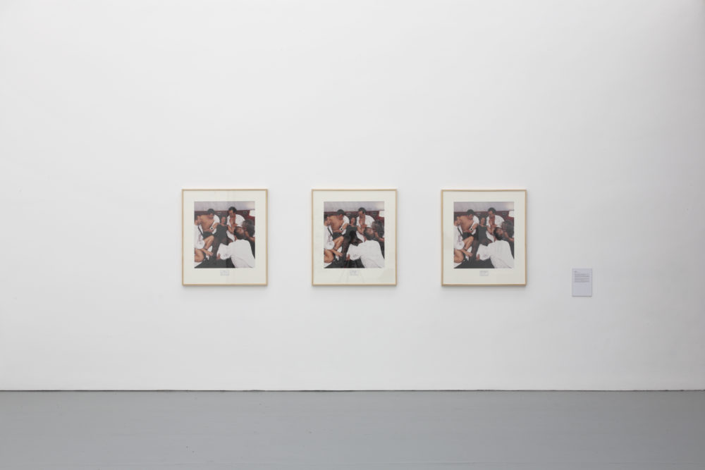 Installation view of Wealth of Nations (2010). The gallery is light and the walls are white. Three identical photographs of people hang on the walls.