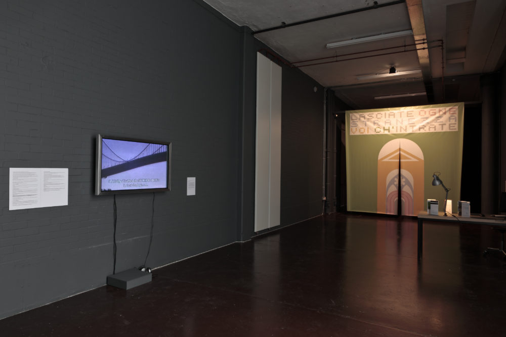 Installation view of Wealth of Nations (2010). The gallery is dim and the walls are painted in dark colours. A curtain with bold graphics is illuminated.