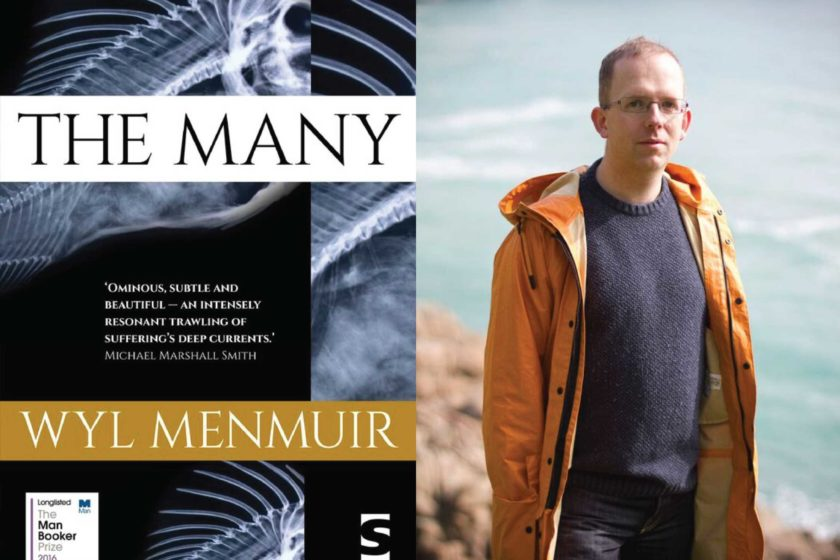 A photograph of the author Wyl Menmuir next to their book The Many.