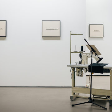 Installation: A desk with a sewing machine on it sits in a gallery, a microphone is set up to pick up the sound of the machine needle. Behind, three simple embroidered drawings hang in frames.