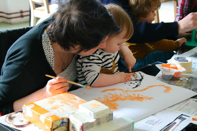 A child of around one years old paints with their fingertip whilst sitting on their carers' lap. Their carer paints with a brush.