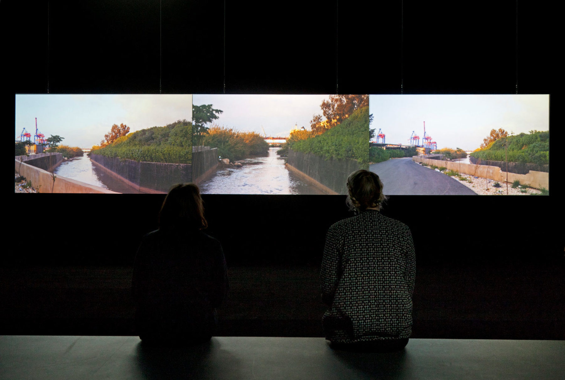 Installation shot: Two visitors study a screen showing three shots of a river.