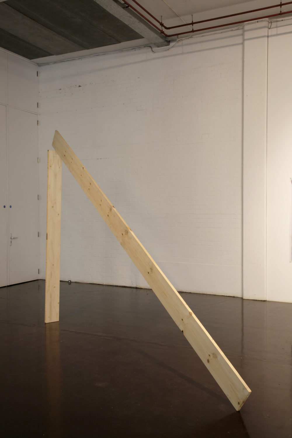 Installation view of Part-ilha, A River Ain't Too Much to Love (2011). A wooden plank stands vertically, and another leans against it.