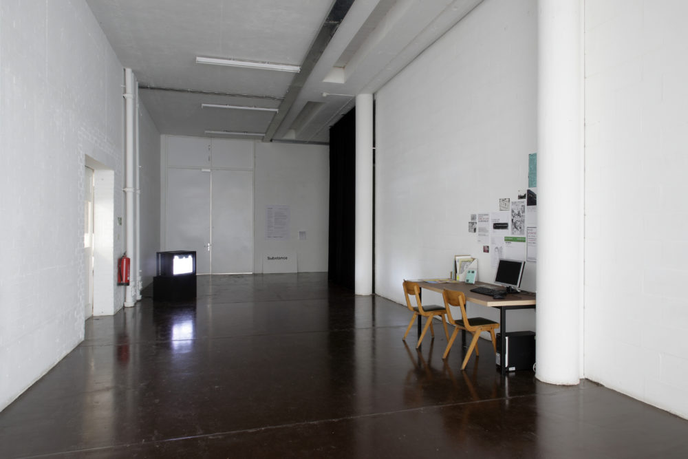 Installation view of Part-ilha, A River Ain't Too Much to Love (2011). A desk sits to the right, a large old television monitor sits in the back, to the left.