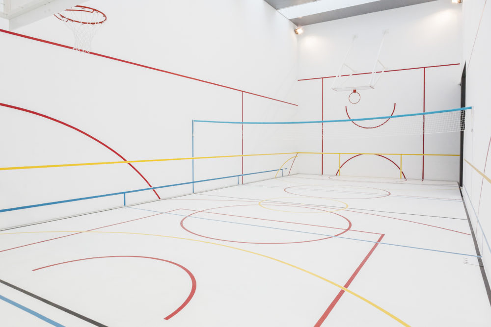 A white gallery space is marked out with colourful lines like a sports hall