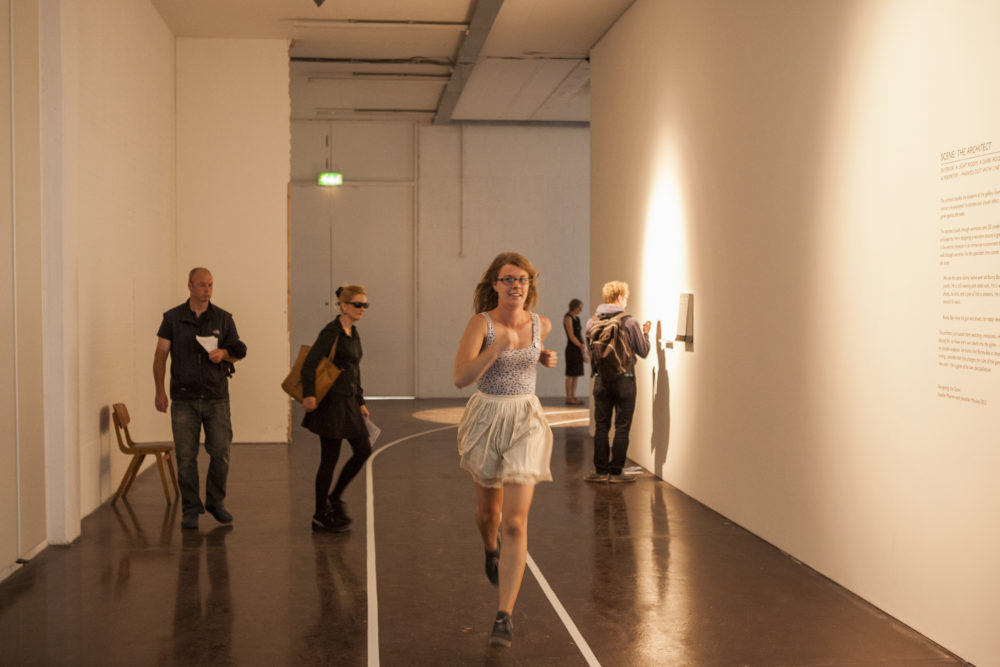 A white walled gallery corridor is marked out with a running track around which a girl is running, past visitors who are exploring the exhibition