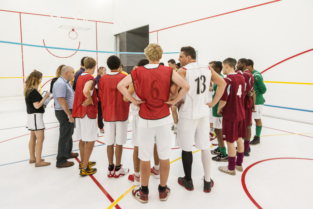 A large group of people wearing sports kit and coloured tabards are gathered together in a white walled gallery marked out with colourful lines like a sports hall