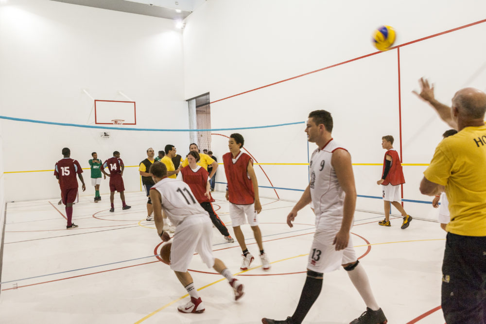 A sports team of people wearing sports kit for playing basketball are gathered together in a white walled gallery marked out with colourful lines like a sports hall