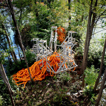 Site-specific installation: a grey structure built amongst forestry with orange tubing woven throughout