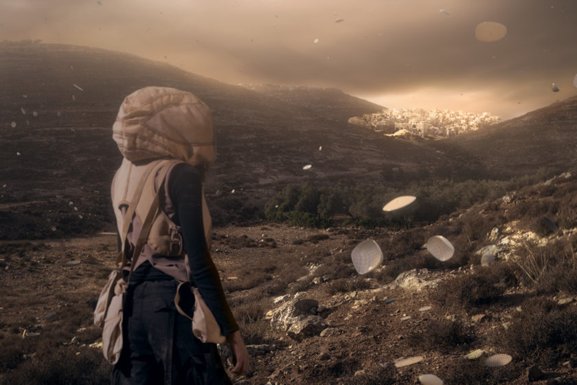 Film still of a figure wearing a hooded jacket looking out towards a hilly landscape with a bright city in far the distance, porcelain type objects float in the air around her