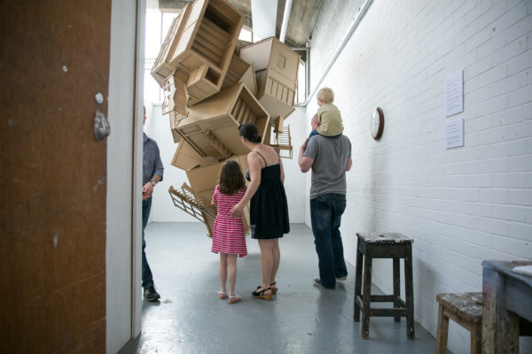 Visitors inside an artists' studio looking at an installation of wooden structures that look like abstracted houses tumbling from the ceiling.