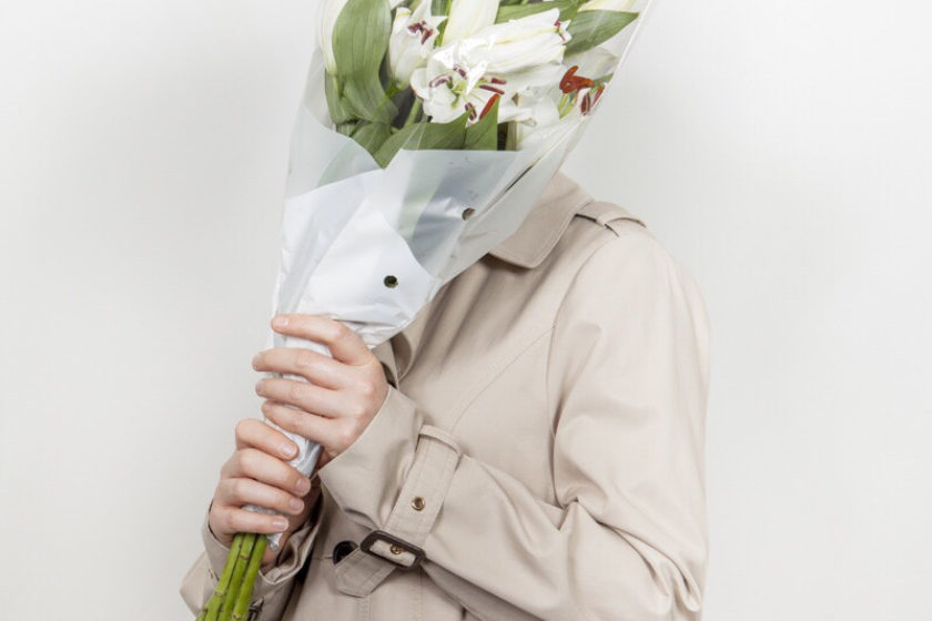 Photograph of a man in a beige mackintosh jacket holding a bunch of white lilies to hide his face