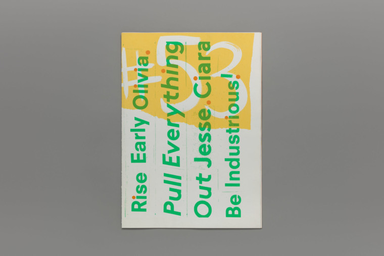 """A closed book. On the cover are the words """"Rise Early Olivia. Pull everything out Jesse. Ciara be industrious!"""" screenprinted in green over a yellow and white graphic background."""