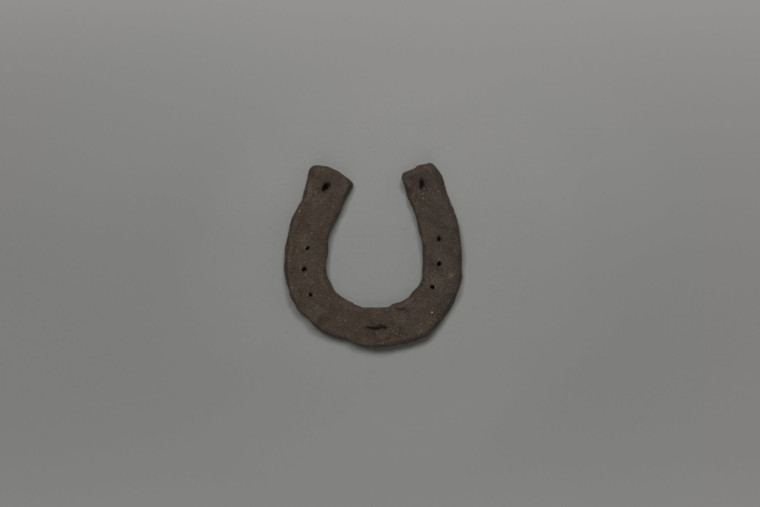 Hand crafted horseshoe in dark clay, photographed against a grey background.
