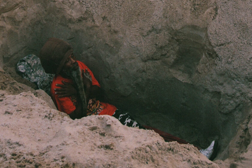 A photograph of a man down a hole on a sandy beach, the top of his head and torso is just visible.
