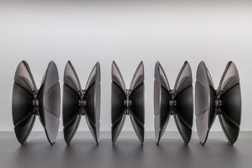 Photograph of five round metal sculptures on the floor in a gallery space, a white wall behind them.