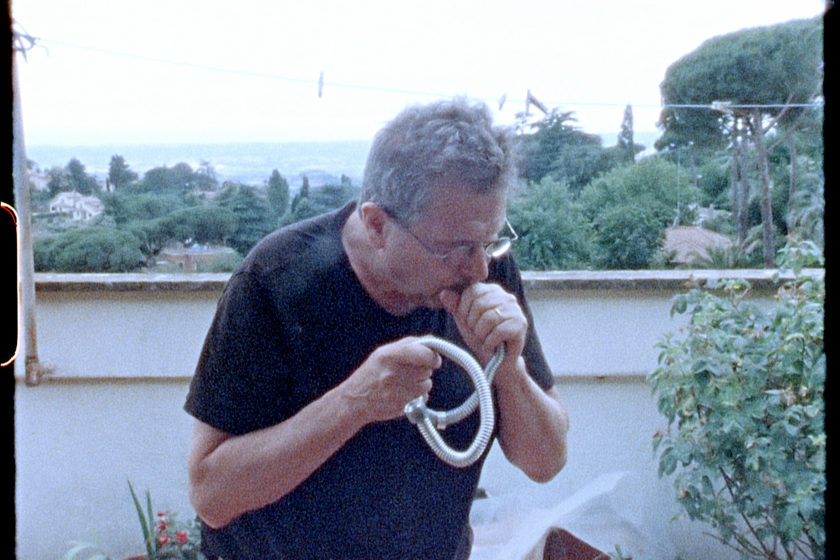 Film still featuring a man with white hair and round glasses and wearing a black tshirt, blowing into a flexible hose.