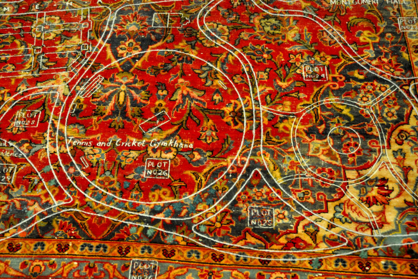 White thread stitched upon an antique Kashan carpet. The carpet has a flowery pattern with red, green, yellow, and blue colours. It is threadbare in some places. The white thread depicts a map with written annotations including