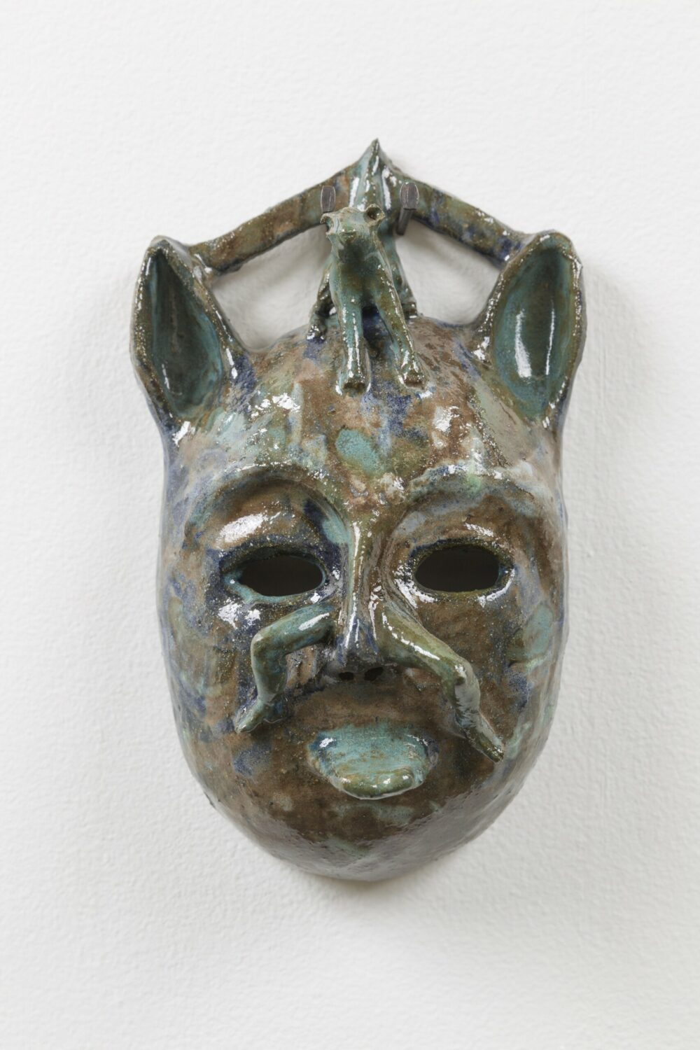A glazed ceramic mask in silver and bronze tones, with ears and hollow eye sockets, and the centre of the face is shaped like the form of a small figure.