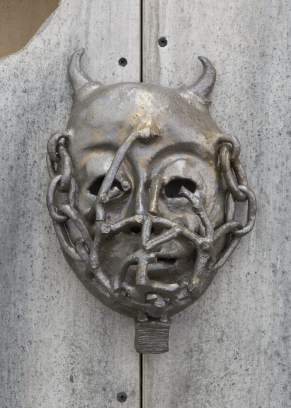 A glazed ceramic mask in silver and bronze tones, featuring a head with small horns, covered in chains which enter into the hollow eye sockets.